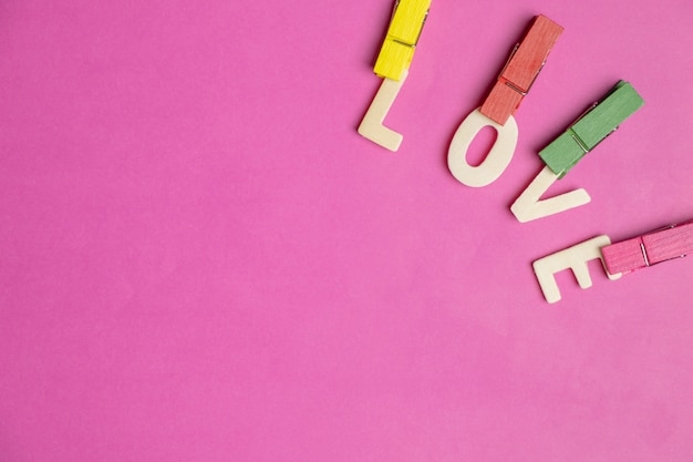 Word love in red hearts on pink background, love icon, valentine's day, relationships concept
