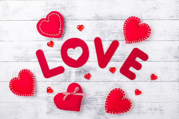 Word love and red hearts on white wooden table. red textile letters. valentines day greeting card