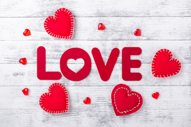 Word love and red hearts on white wooden table