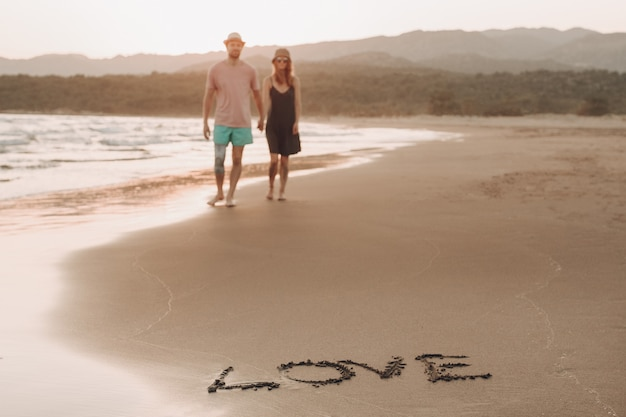 Word love on the sand coast and blurred loving couple on background walking