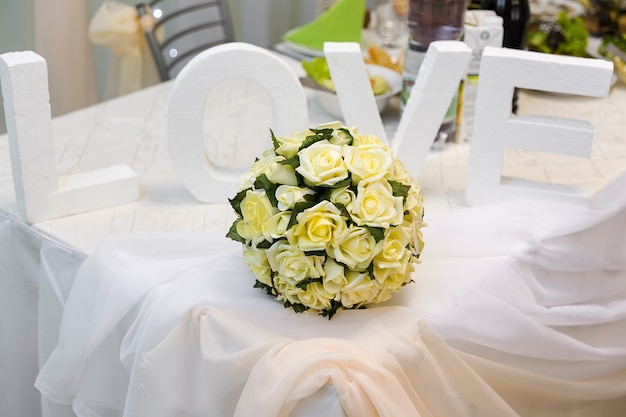 Word love and wedding bouquet on table