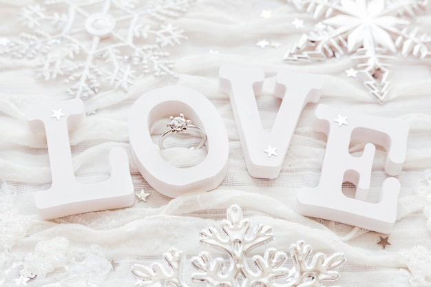 Word love on white fabric background with engagement diamond ring