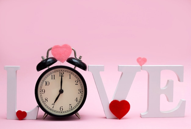 Word love with a clock instead of the letter o