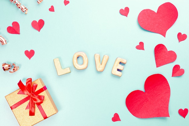 Word love with gold gifts, red paper hearts, confetti. sweet holiday background, small hearts.