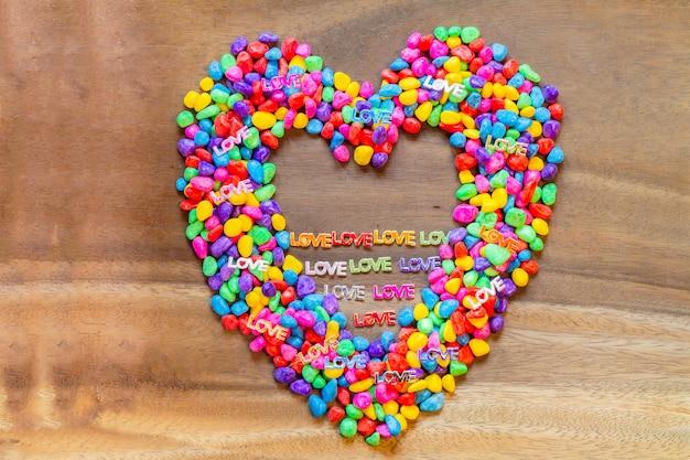 Слово любовь с днем святого валентина в форме сердца с абстрактным цветом камней на фоне дерева