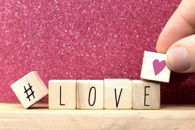 Word love on wooden cubes with pink heart and hashtag