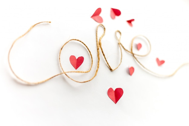 Word love written with rope, paper hearts around focused on paper heart in letter o