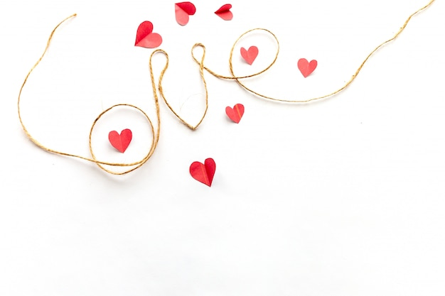 Word love written with rope, on white background, paper hearts around