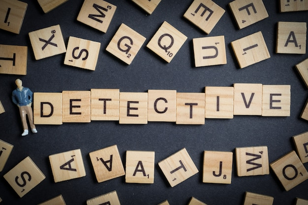 Word made of wooden letters - detective, on black  with abstract male model. investigation profession .