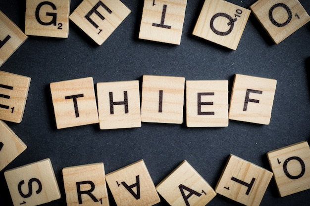 Word made of wooden letters - thief, on black. crime designation .