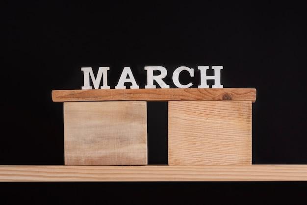 黒の背景に木製の棚の木製ブロックに書かれた単語行進
