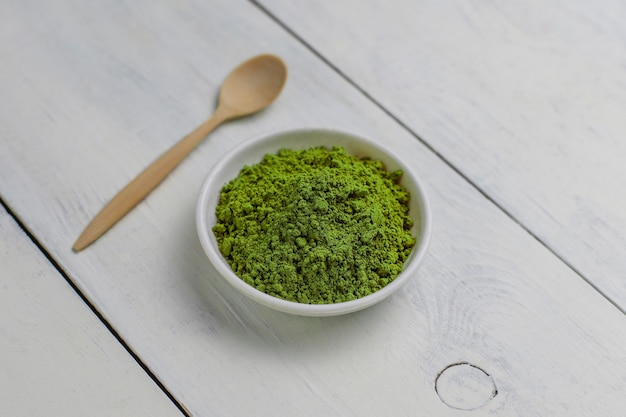 Word matcha made of powdered matcha green tea and bamboo spoon on white . copy