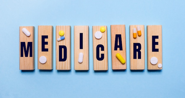 The word medicare is written on wooden blocks on a light blue table near the pills. medical concept.
