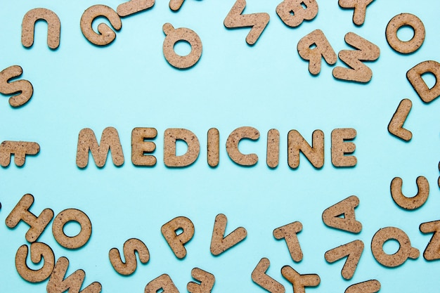 The word medicine among many wooden letters on blue surface.