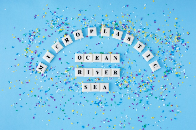 Word microplastic ocean river sea around small plastic particles on a blue background.