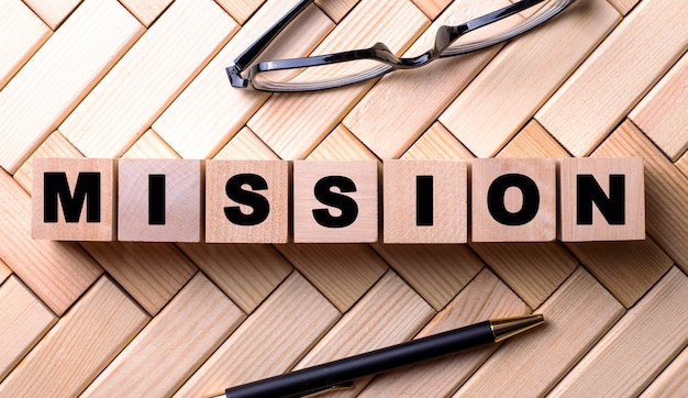 The word mission is written on wooden cubes on a wooden surface next to a pen and glasses