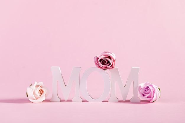 パステルピンクの背景に花で飾られた単語「ママ」