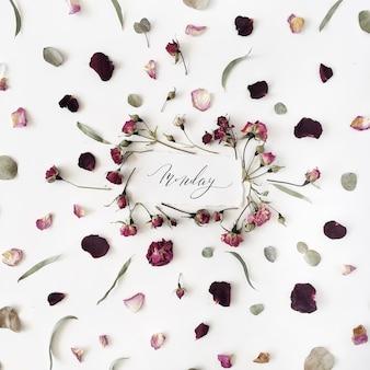 Слово понедельник, написанное в стиле каллиграфии на бумаге с розовыми, красными розами, эвкалиптом и листьями на белом