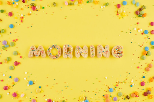 작은 달콤한 사탕과 뿌리가있는 노란색 테이블에 수제 쿠키 알파벳에서 배열 된 단어 아침