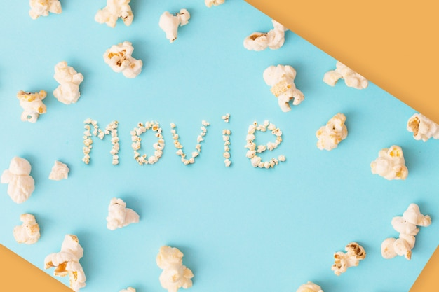 Word movie made of popcorn on blue and orange surface