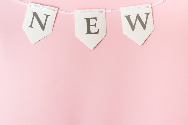 Word new on pastel pink background, top view with copy space