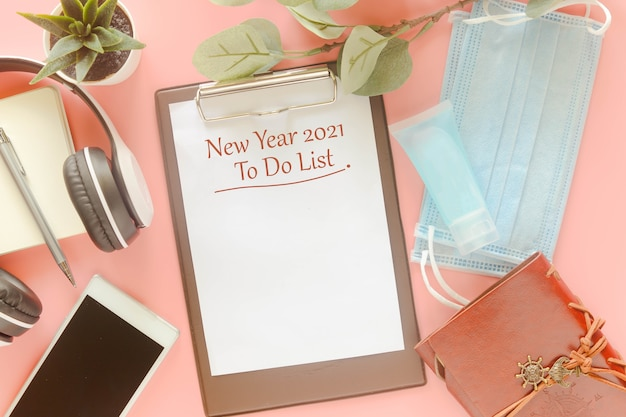 Word new year 2021 to do list on clipboard with stationery, mask and hand sanitizer. concept to present to do list in new year 2021, new normal post covid-19 pandemic.