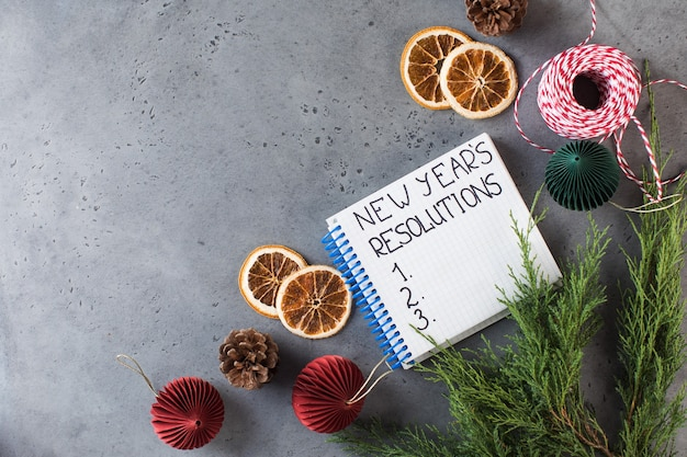 The word new years resolution written in a white notebook on a gray new years background copy space
