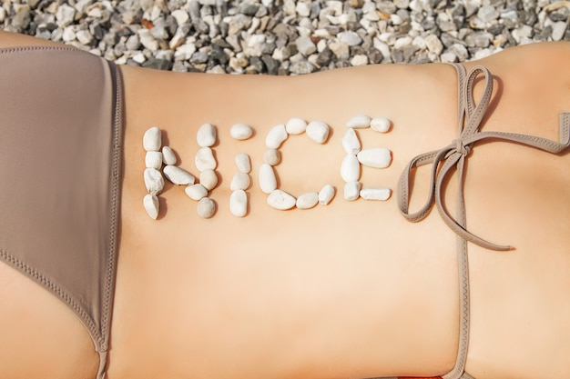 The word nice in pebbles on a back of the woman sunbathing on the beach