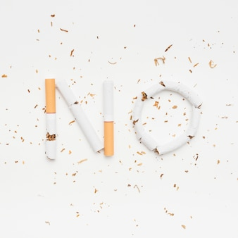 Word no made from broken cigarette with tobacco on isolated on white background