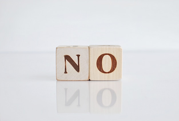 Word no on white background with reflection, negative answer.