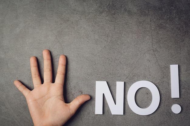 暗い壁に子供の手で「いいえ」という言葉