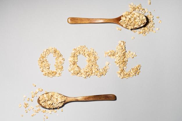 Слово oat из хлопьев и овса на деревянной ложке на сером фоне.