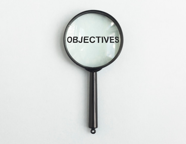Word objectives through magnifying glass on light blue gary background target concept