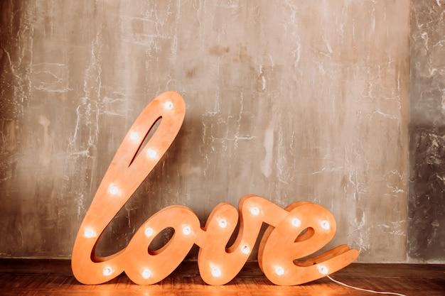 愛の言葉。懐中電灯が付いている手紙。インテリアの明るい言葉の愛。床に電球のついた巨大な文字。