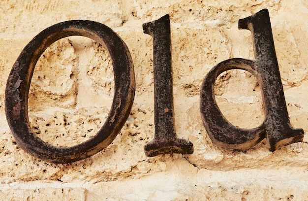 The word old in metal letters on stone background.