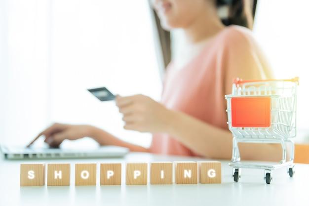 온라인 결제에서 신용 카드를 사용하여 온라인 쇼핑을 하는 알아볼 수 없는 아시아 젊은 여성, 나무 큐브 쇼핑 및 흉내낸 쇼핑 카트에 대한 단어. 온라인 구매를 하는 행복한 소녀.