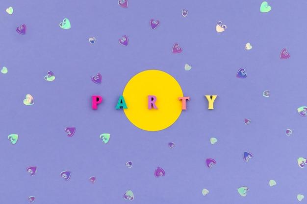 紫の背景に木製のカラフルな文字からのワードパーティー
