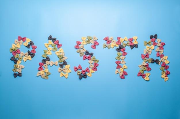 Слово макароны из макарон фарфалле разных цветов на синем фоне