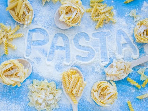 さまざまな種類と形の乾燥したイタリアンパスタと小麦粉の木製テーブルの上の単語パスタ。トップビューフラットレイアウト