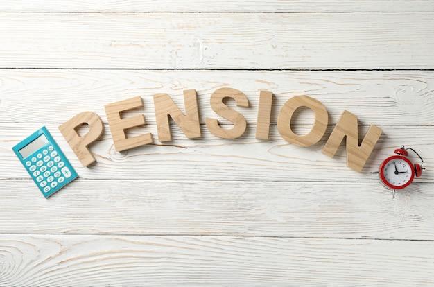 Word pension, калькулятор и будильник на деревянной поверхности