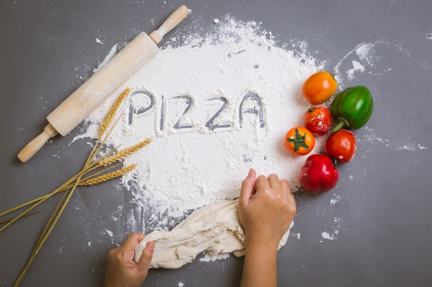 Word pizza written on flour with ingredients