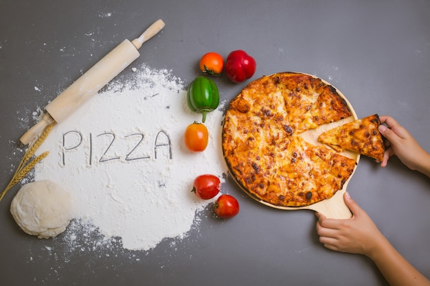 Word pizza written on flour with a tasty pizza