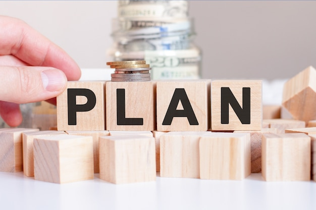 The word plan on the wooden blocks and a bank with money behind, business concept