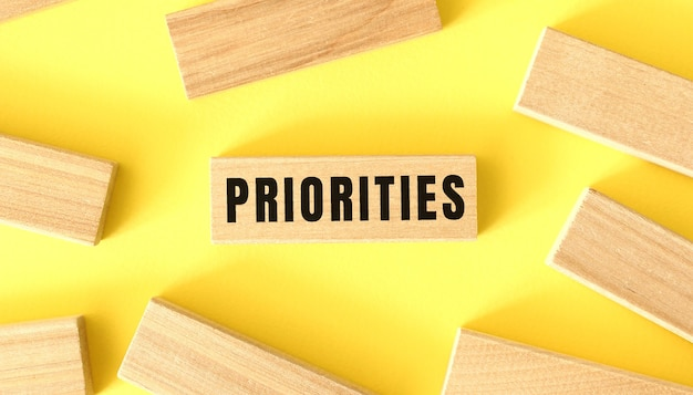 The word priorities is written on a wooden blocks on a yellow background