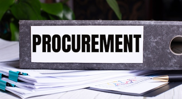 The word procurement is written on a gray file folder next to documents. business concept