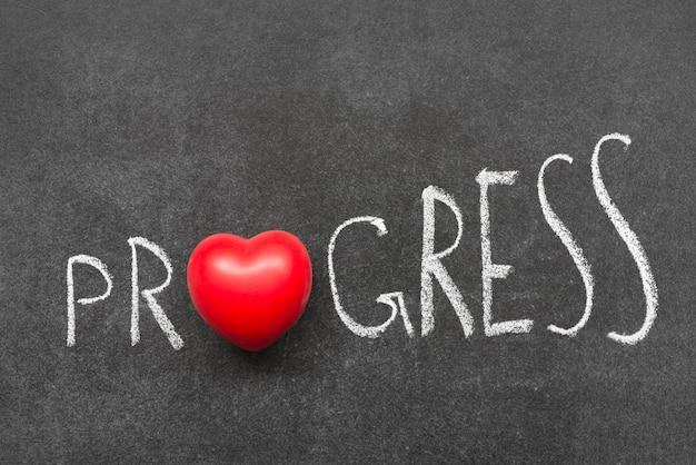 Слово прогресс написано от руки на доске с символом сердца вместо o