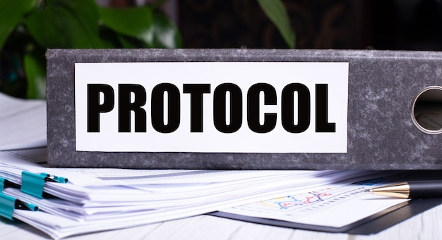 The word protocol is written on a gray file folder next to documents