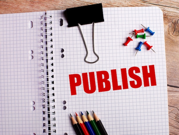 The word publish is written in a notebook near multi-colored pencils and buttons on a wooden wall.