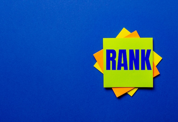 The word rank is written on bright stickers on a blue surface