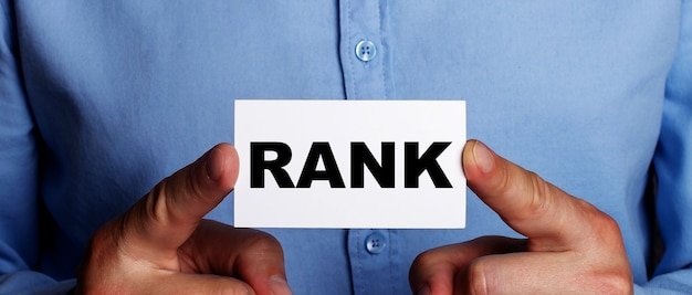 The word rank is written on a white business card in a man's hands. business concept